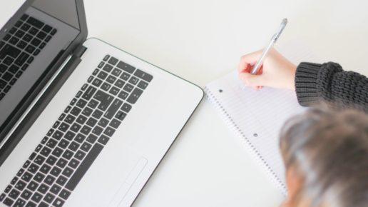 girl taking notes at computer