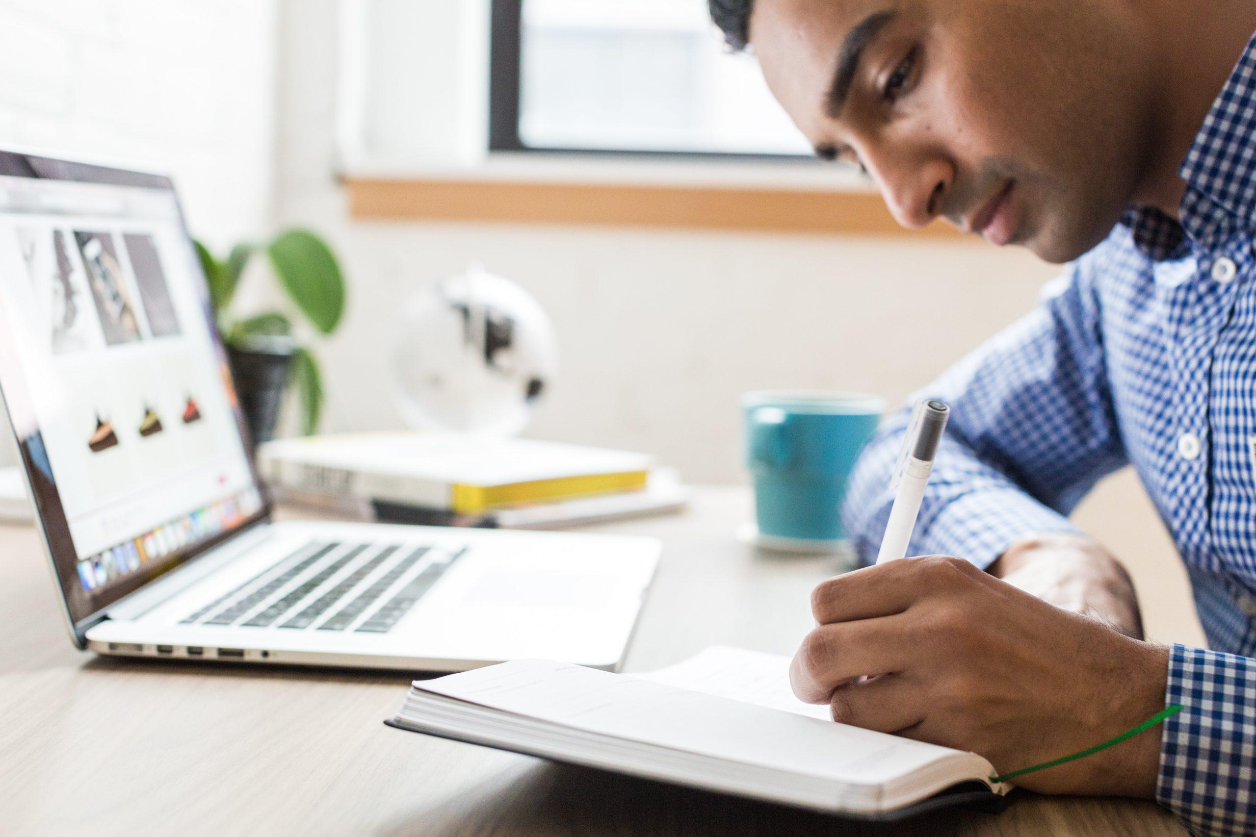 man taking notes at the computer
