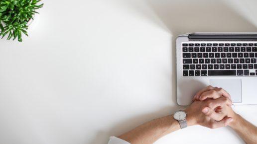 hands folded over laptop