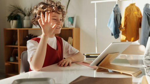 kid waving at a laptop camera