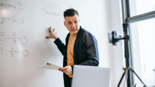 man referencing whiteboard and teaching to a camera