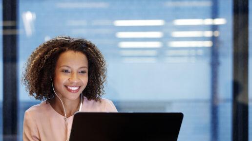 Young smiling businesswoman wearing earphones, using laptop