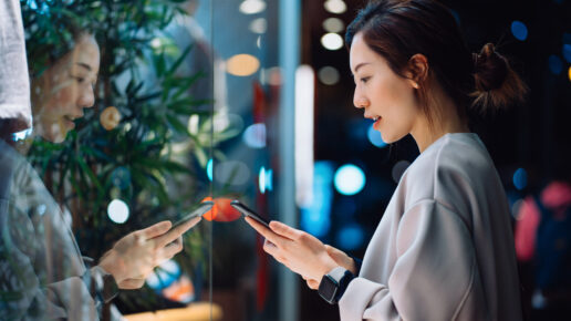 woman looking at phone in front of shop window